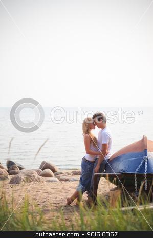 beautiful couple on a beach stock photo, beautiful couple on a beach near old boat by Petr Malyshev