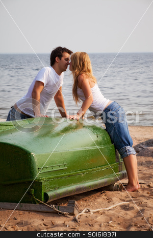 beautiful couple kissing on a beach stock photo, beautiful couple kissing on a beach near old boat by Petr Malyshev
