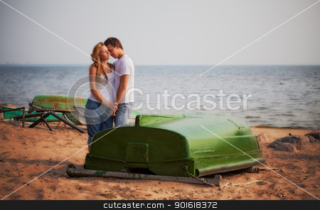 couple embrace on a beach stock photo, beautiful couple embrace on a beach by Petr Malyshev