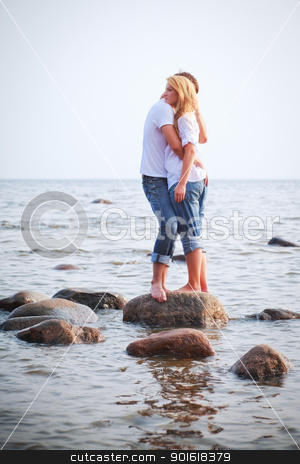 couple embrace on a stone in sea stock photo, couple embrace on a big stone in sea by Petr Malyshev