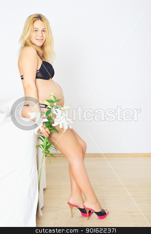 Pregnant Woman with Flower stock photo, pregnant woman standing in room with white lily by Petr Malyshev