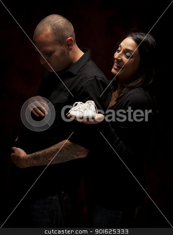 Mixed Race Couple Holding New White Baby Shoes on Black stock photo, Fun Mixed Race Couple Holding New White Baby Shoes Against a Black Background Under Dramatic Lighting. by Andy Dean
