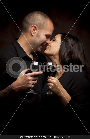 Happy Mixed Race Couple Holding Wine Glasses stock photo, Happy Young Mixed Race Couple Holding Wine Glasses Against A Black Background. by Andy Dean