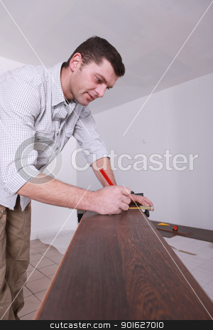 Man marking parquet floor before cutting to size stock photo, Man marking parquet floor before cutting to size by photography33