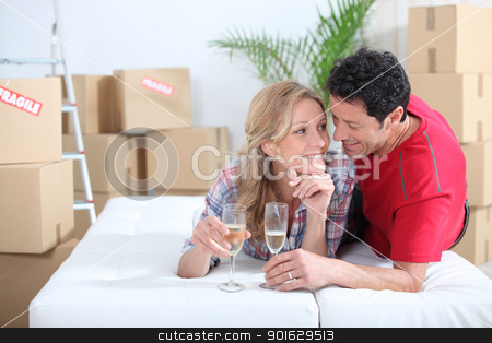 Couple lying on bed celebrating moving into new home stock photo, Couple lying on bed celebrating moving into new home by photography33