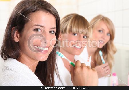 Three female house mates brushing their teeth stock photo, Three female house mates brushing their teeth by photography33
