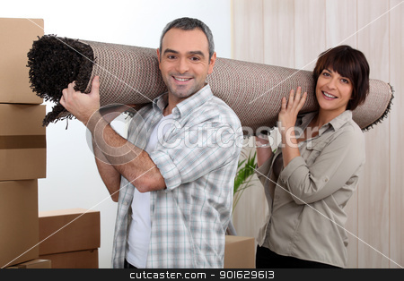 Couple carrying carpet over shoulders stock photo, Couple carrying carpet over shoulders by photography33