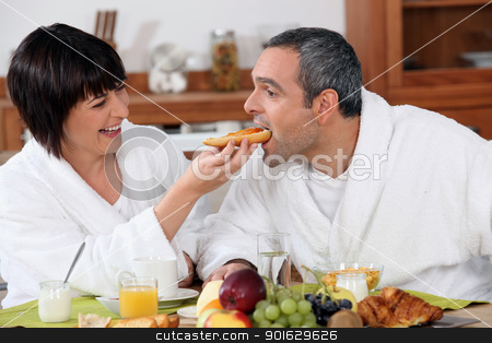Playful couple having breakfast stock photo, Playful couple having breakfast by photography33