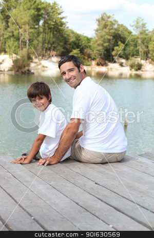 Father and son sitting by lake stock photo, Father and son sitting by lake by photography33