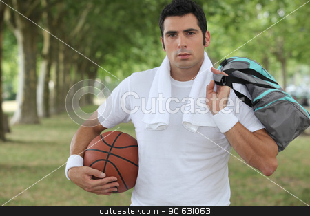 30 years old sportyman holding a basket ball and a sports bag stock photo, 30 years old sportyman holding a basket ball and a sports bag by photography33