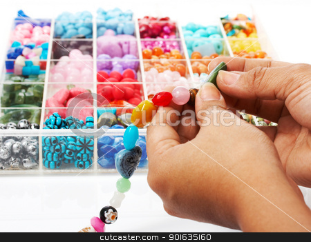 Choosing Beads For A Unique Necklace stock photo, Selecting Beads In An Assortment Of Colors For A Beautiful Unique Necklace by stuartmiles