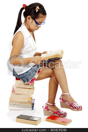 Young Preschooler Reading A Book stock photo, Young Preschooler Sitting On A Pile Of Books And Reading One by stuartmiles