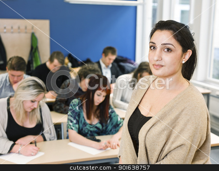 Teacher in classroom stock photo, Schoolteacher in front of pupils in the classroom by Anne-Louise Quarfoth