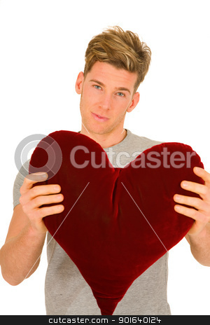 young man with a heart shaped pillow stock photo, young man with a heart shaped pillow by ambrophoto