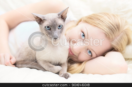 Playing With Cat stock photo, beautiful blond girl playing with cat in a bed by Petr Malyshev