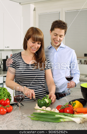 Young couple preparing salad stock photo, Photo of a young couple preparing salad in their kitchen and drinking wine. by © Ron Sumners
