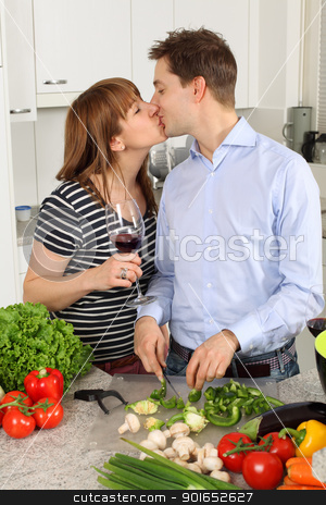 Young couple kissing in their kitchen stock photo, Photo of a young couple kissing in their kitchen while preparing food and drinking wine. by © Ron Sumners