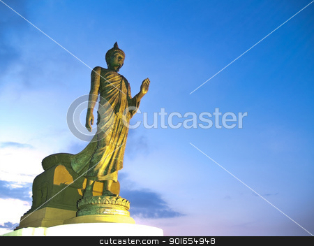 Walking Buddha image stock photo, Walking Buddha image in Vitarka Mudra posture illuminate with spotlight at twilight time, Buddhamonthon, Nakhon Pathom, Thailand by Exsodus