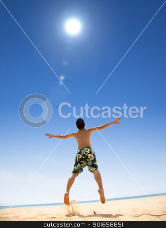 happy young man jumping on the beach stock photo, happy young man jumping on the beach by tomwang