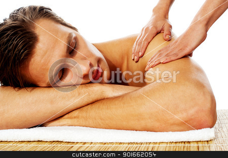 Attractive man having massage in a spa center stock photo, Close-up of an attractive man enjoying a back massage in a spa center by Ishay Botbol