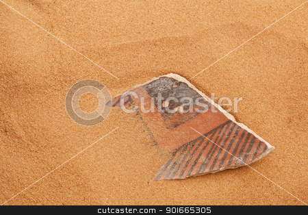 Anasazi pottery shard in red sand stock photo, ancient Anasazi pottery shard buried in red desert sand by Marek Uliasz