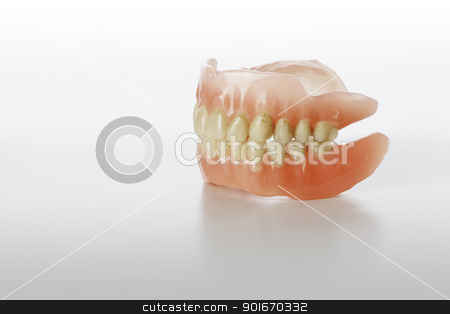 Old Dentures stock photo, Old Stained Dentures on light grey background. by Stocksnapper