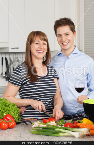 Happy couple in their kitchen stock photo, Photo of a young couple preparing salad in their kitchen and drinking wine. by © Ron Sumners