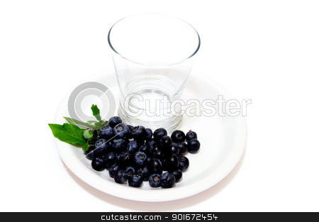 Fresh picked Blueberries and empty glass stock photo, Blueberries and an empty juice glass on a white plate with a light colored background by Lynn Bendickson