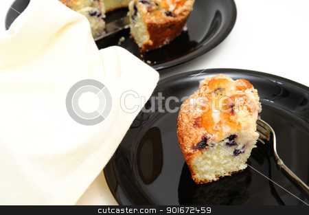 Blueberry Ring Cake stock photo, Slice of fresh baked Blueberry Ring Cake served on a black plate with a light colored background by Lynn Bendickson