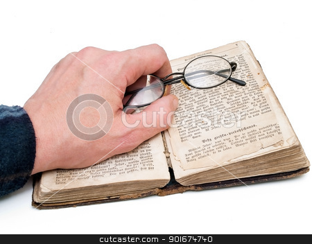 old book reading stock photo, Man hand with glasses at the old book over white background by Sergej Razvodovskij