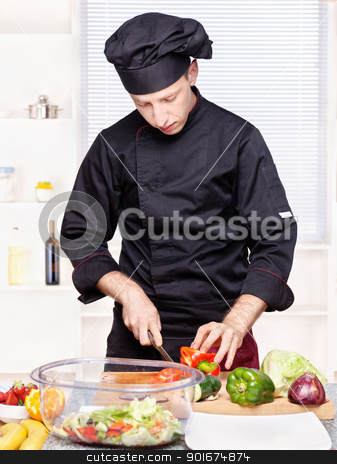 chef cutting bell peppers in kitchen stock photo, chef in black uniform cutting bell peppers on board by iMarin