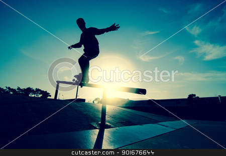 Skateboarder silhouette on a grind stock photo, Skateboarder silhouette on a grind at the local skatepark. by Homydesign