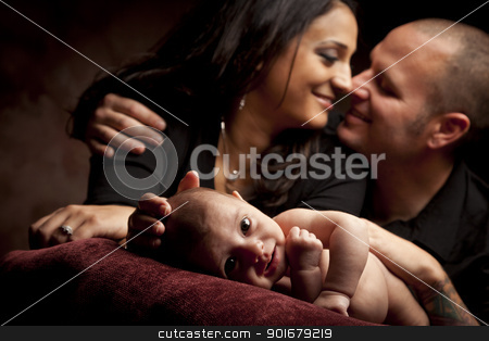 Mixed Race Couple Lovingly Look On While Baby Lays on Pillow stock photo, Mixed Race Couple Lovingly Look On While Baby Lays on Pillow on a Dark Background. by Andy Dean