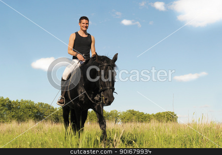young man and horse stock photo, young man and his black stallion in  a field by Bonzami Emmanuelle