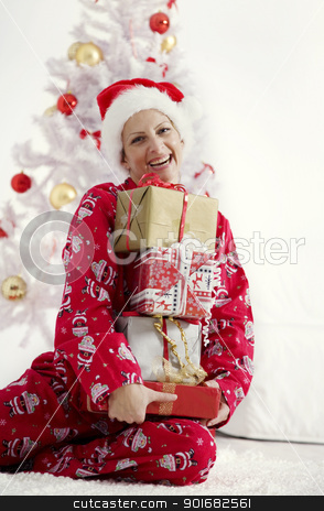christmas  stock photo, young woman in christmas pajamas holding a bunch of christmas presents by Liv Friis-Larsen