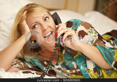 Woman Laying on Her Bed Using the Telephone stock photo, Beautiful Blonde Woman Laying on Her Bed Using the Telephone. by Andy Dean