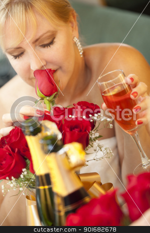 Blonde Woman Smells Roses at Mirror Near Champagne stock photo, Attractive Blonde Woman Smells Roses at Mirror Near Champagne. by Andy Dean