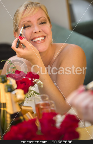 Blonde Woman Applies Makeup at Mirror Near Champagne and Roses stock photo, Attractive Blonde Woman Applies Her Makeup at a Mirror Near Champagne and Roses. by Andy Dean
