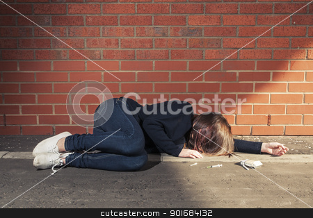Addicted (fourth in the series) stock photo, Addicted, sad young woman lying against the brick wall with syringe and cigarettes beside.  Horizontal. by nowoka1na