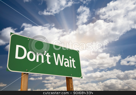 Don't Wait Green Road Sign and Clouds stock photo, Don't Wait Green Road Sign with Dramatic Clouds, Sun Rays and Sky. by Andy Dean