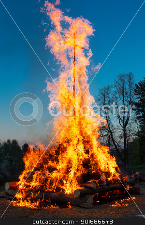 walpurgis night stock photo, walpurgis night burning wood and religion cross with huge flames by Artush