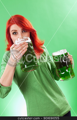 Redhead enjoying green beer stock photo, Photo of a beautiful redhead holding two huge mugs of green beer and drinking from one, on St. Patricks Day. by © Ron Sumners