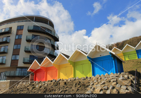 Beach chalets and tourst hotel stock photo, Beach chalets and tourist hotel building with blue sky and cloudscape background. by Martin Crowdy