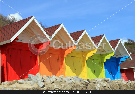 Beach huts or chalets stock photo, Row of colorful beach huts or chalets with blue sky background and copy space. by Martin Crowdy