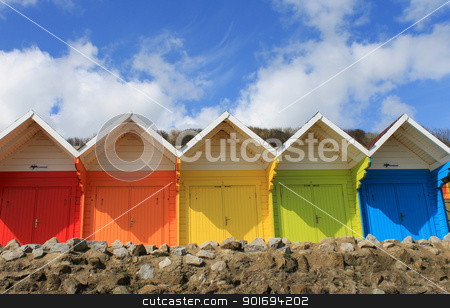 Colorful beach chalets stock photo, Row of colorful beach chalets with blue sky and cloudscape background, summer scene. by Martin Crowdy