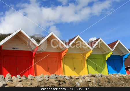 Colorful beach huts stock photo, Row of colorful beach huts with blue sky and cloudscape background, summer beach scene. by Martin Crowdy