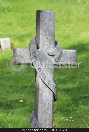 Cross in cemetery stock photo, Memorial cross gravestone in cemetery with green grass in background. by Martin Crowdy