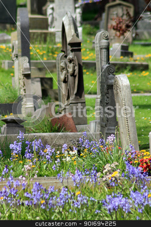 Old graves in cemetery stock photo, Old graves in cemetery with flowers in foreground. by Martin Crowdy