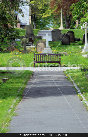 Path and bench in old cemetery stock photo, Path and bench in old cemetery with church and gravestones. by Martin Crowdy