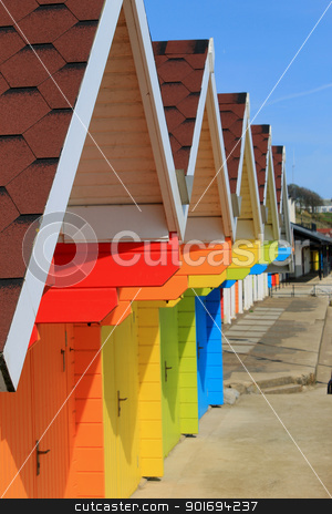 Row of colorful beach huts or chalets stock photo, Row of colorful beach huts or chalets with blue sky background and copy space. by Martin Crowdy